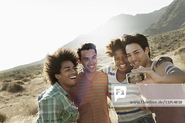 Eine Gruppe von Freunden  Männer und Frauen  geht gemeinsam in der Hitze des Tages für ein Selfy in Pose.