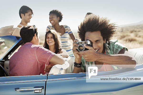 A group of friends in a pale blue convertible on the open road  one holding a camera and taking photographs.