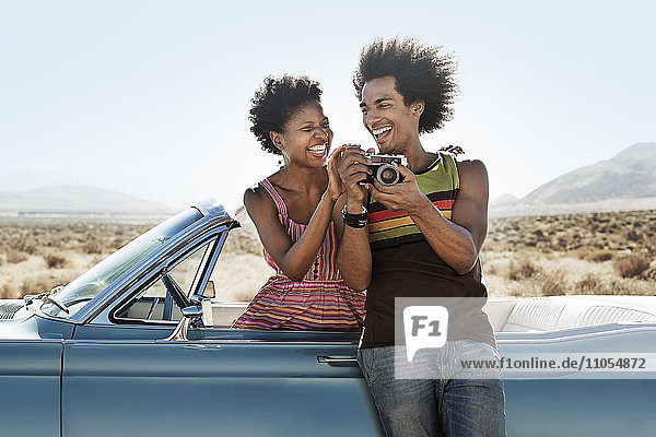 A young couple  man and woman in a pale blue convertible on the open road