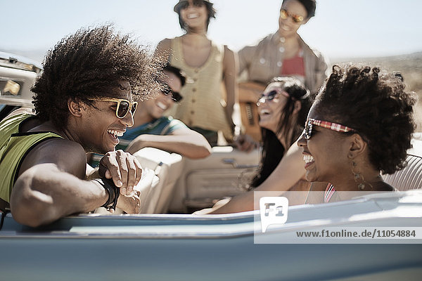 A group of friends in a pale blue convertible on the open road  driving across a dry flat plain surrounded by mountains.