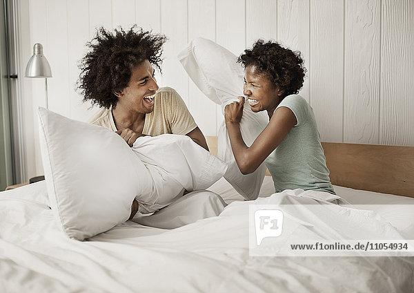Ein junges Paar sitzt im Bett und streitet mit Kissen.