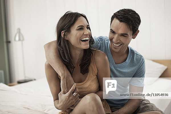 A young couple sitting together on the edge of a bed  laughing and hugging.