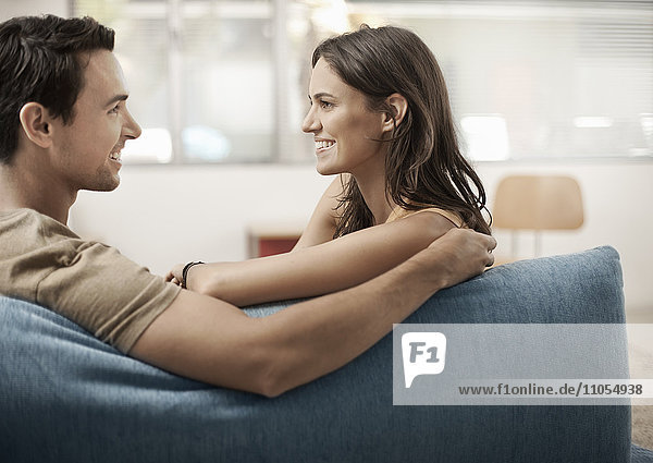 A young couple sitting on a sofa  gazing at each other  a man and woman  boyfriend and girlfriend.