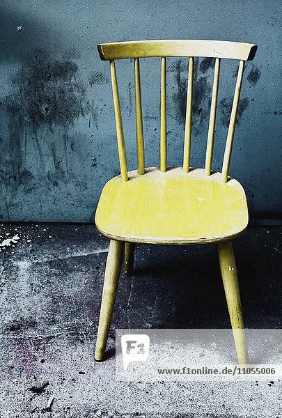 Hölzerner Stuhl links in einer Gasse.