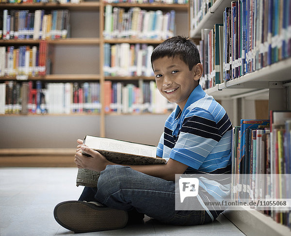 A boy sitting on the floor in a library reading a book.