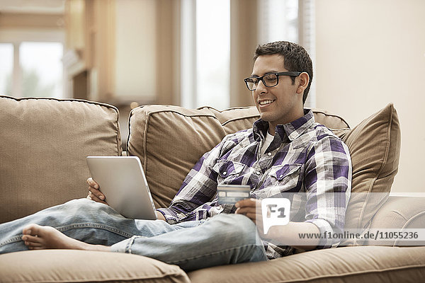 A man sitting on a sofa using a digital tablet and holding a credit card.