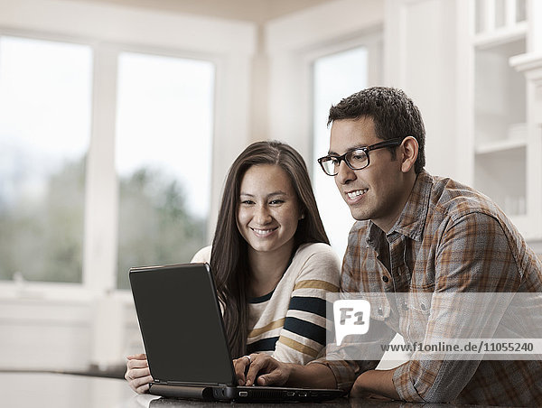 A couple sitting using a laptop computer.