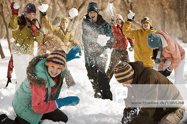 Eine Gruppe von Jugendlichen  Jungen und Mädchen  die eine Schneeballschlacht veranstalten.
