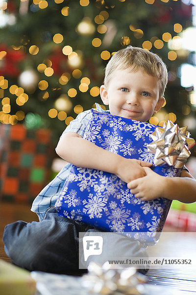 A young boy by a Christmas tree hugging a large wrapped present.