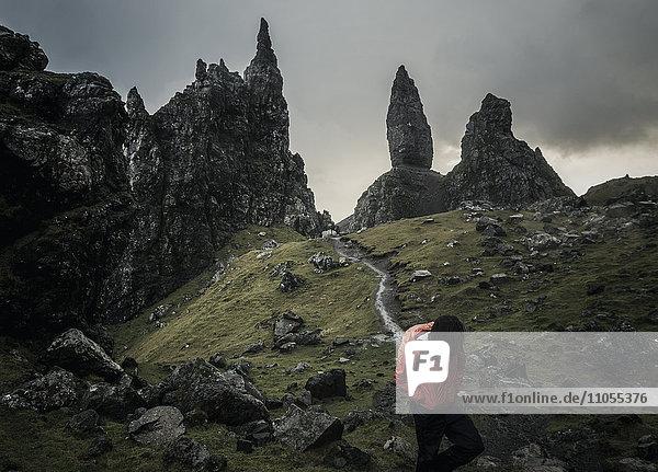 Zwei Personen mit Rucksäcken auf einem schmalen Pfad  der zu einer dramatischen Landschaft aus Felsspitzen in der sie überragenden Skyline führt  unter einem bedeckten Himmel mit niedriger Bewölkung.