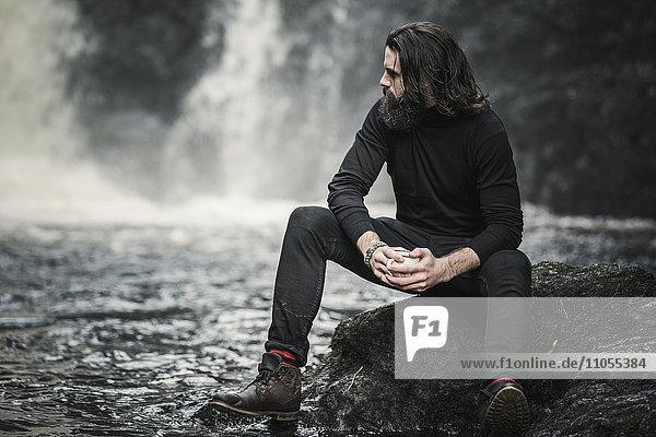 Ein Mann sitzt an einem schnell fließenden Wasserstrom über Felsen.