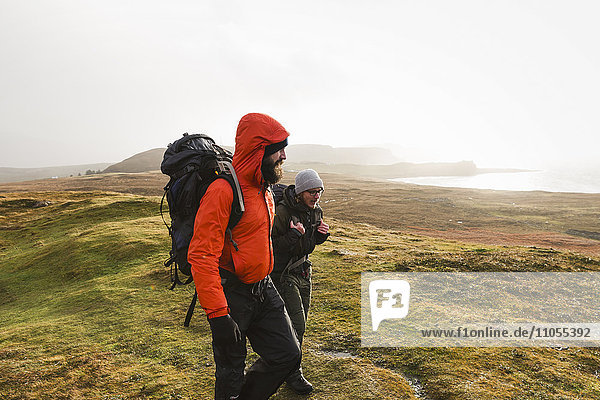 Two men walking with rucksacks  hiking across open ground with a view into the distance of mountains and sea coast.