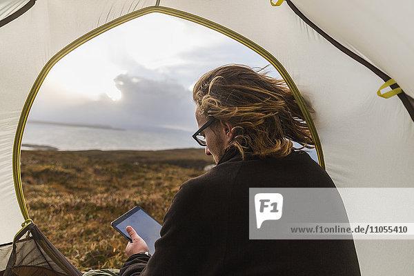 Ein Mann sitzt im Schutz eines Zeltes  schaut hinaus und hält ein digitales Tablet