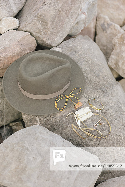 A wide brimmed hat and jewellery  personal belongings left on a rock.