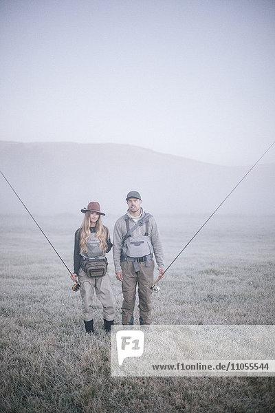 Zwei Personen  die im Frühnebel mit Angelruten über eine Wiese laufen.