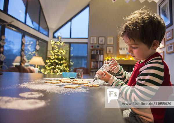 Ein Junge in einer roten Schürze schmückt Weihnachtsplätzchen mit einer Vereisungspistole.