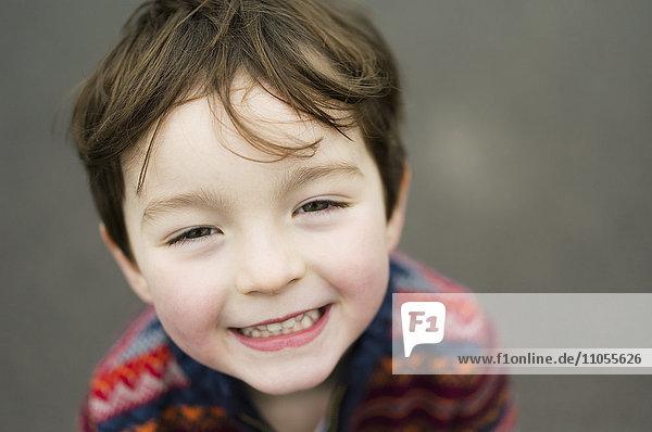 Ein Junge  der in die Kamera schaut und lächelt.