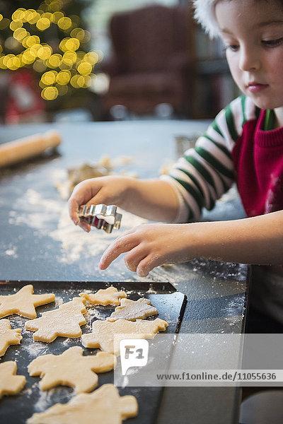 Ein Junge mit Weihnachtsmannmütze  der Weihnachtsplätzchen herstellt und Formen ausschneidet.