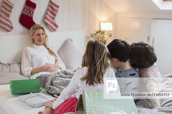 Eine Frau im Bett  mit drei Kindern am Fußende des Bettes  die Weihnachtsgeschenke tragen.