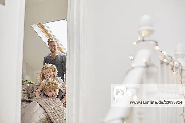Zwei Kinder und ein Mann in einem Schlafzimmer  die aufgeregt durch die Tür schauen.