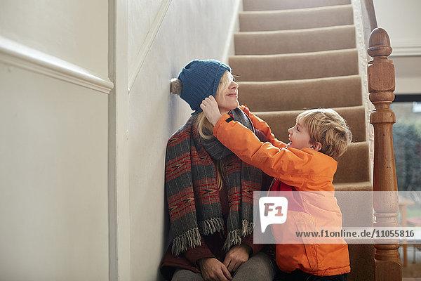 Ein Junge  der seiner Mutter einen Hut über die Augen zieht.