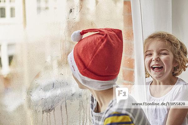 Weihnachtsmorgen in einem Familienhaus. Ein Junge mit Weihnachtsmannmütze  der aus einem Schlafzimmerfenster schaut  und seine Schwester  die neben ihm lacht.
