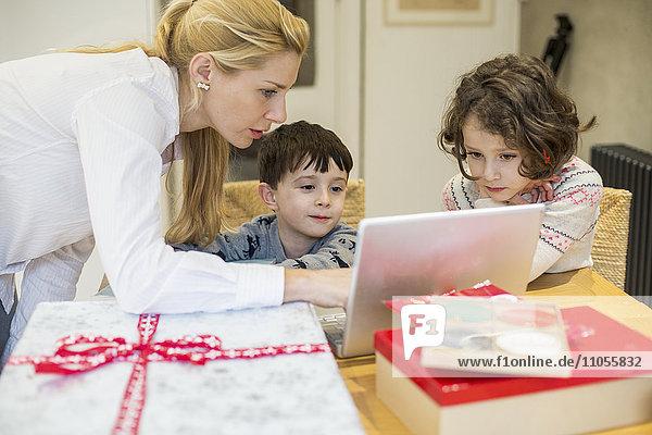 Zwei Kinder und ihre Mutter schauen auf einen Laptop-Computerbildschirm um einen Küchentisch herum.