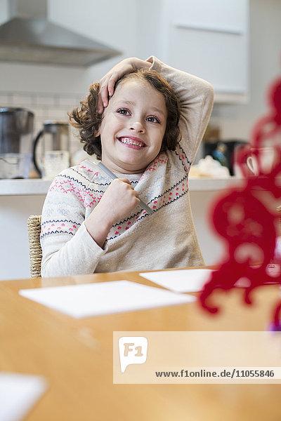 Ein Kind  ein Mädchen  das zu Hause an einem Tisch sitzt und vor Weihnachten Karten zeichnet und schreibt.