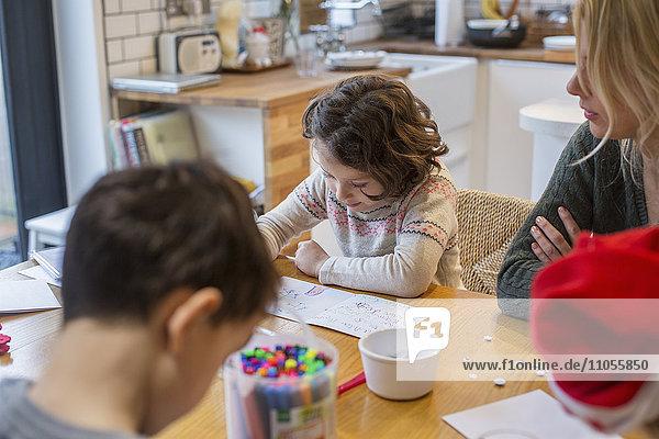 Drei Kinder und eine erwachsene Frau an einem Tisch  malen und schreiben Karten und Briefe an den Weihnachtsmann.