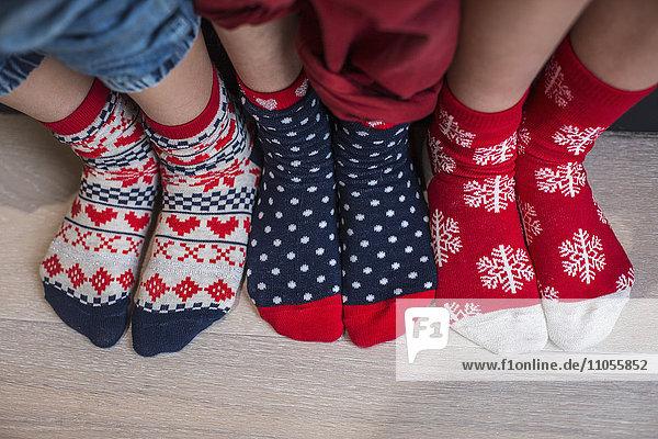 Drei Paar Kinderfüße in bunt gemusterten Weihnachtssocken.