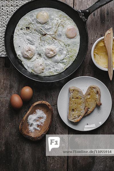 Ein Gericht aus Eiern  Brot und Sauce  das auf einem Tisch steht.