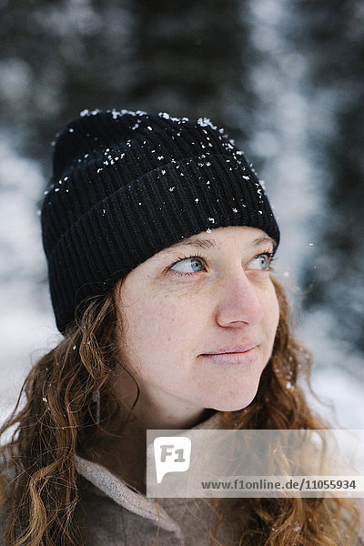 A woman in a black hat dusted with snow outdoors.