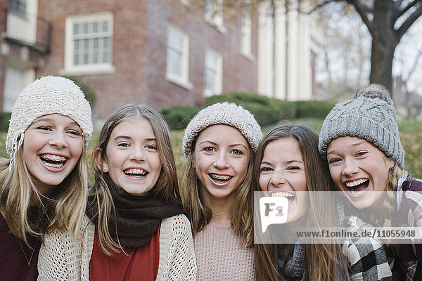 A group of five teenage girls outdoors in woolly hats and scarves.