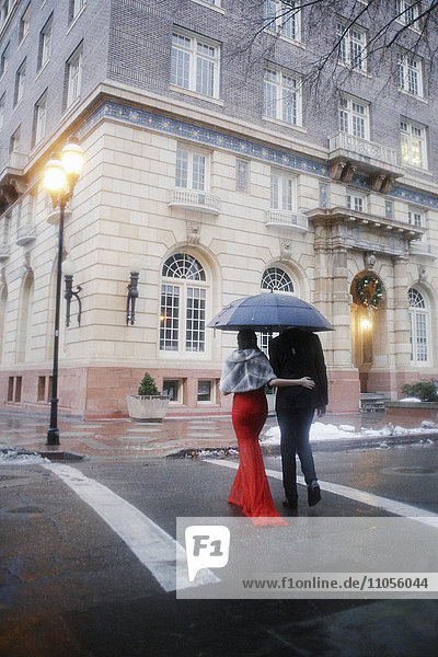 Eine Frau in einem langen roten Abendkleid mit Fischschwanzrock und Pelzstola und ein Mann in einem Anzug  die eine verlassene Straße der Stadt überqueren.