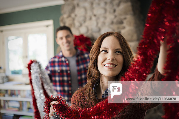 A young couple hanging tinsel up  decorating a house at Christmas.