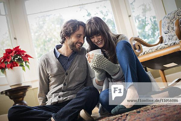 Ein Paar  Mann und Frau sitzen eng beieinander und wärmen sich mit den Händen um Tassen herum auf.