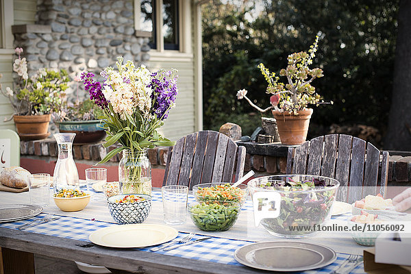 A table set for a meal outdoors in a garden.