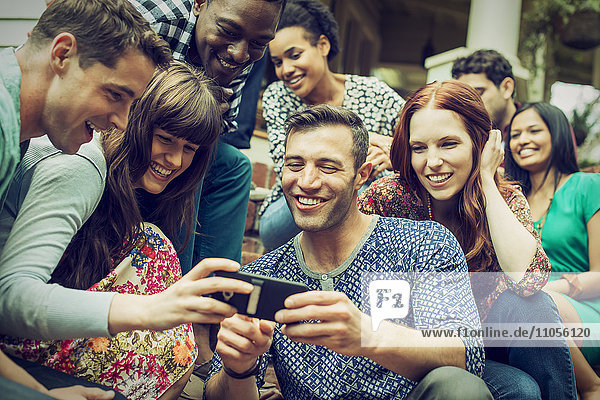 A group of friends on the steps of a house porch  looking at a smart phone selfy on the screen.