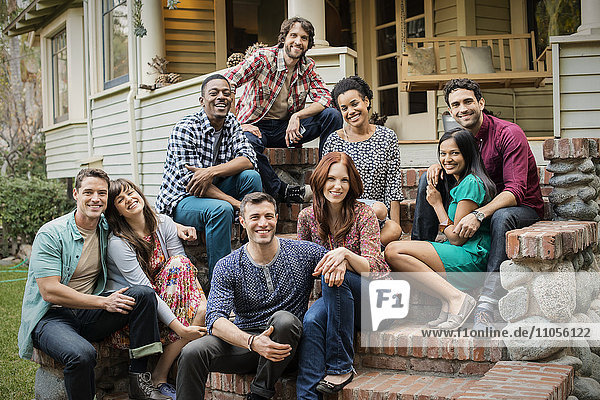 A group of friends sitting on the steps of a house porch  posing and laughing.