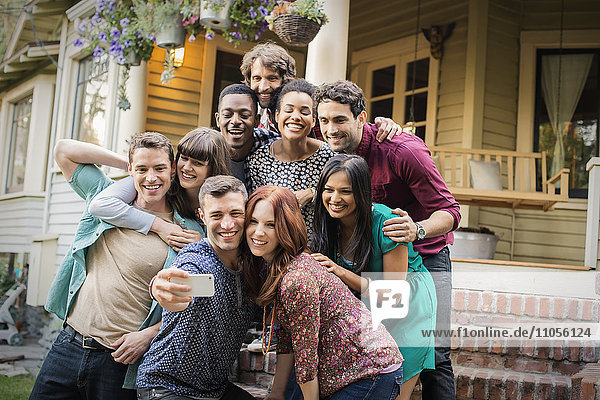 A group of friends posing on the steps of a house porch  taking a group selfy.