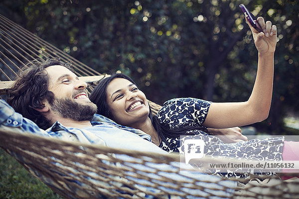 A couple  a young man and woman lying in a large hammock in the garden  taking a selfy of themselves.