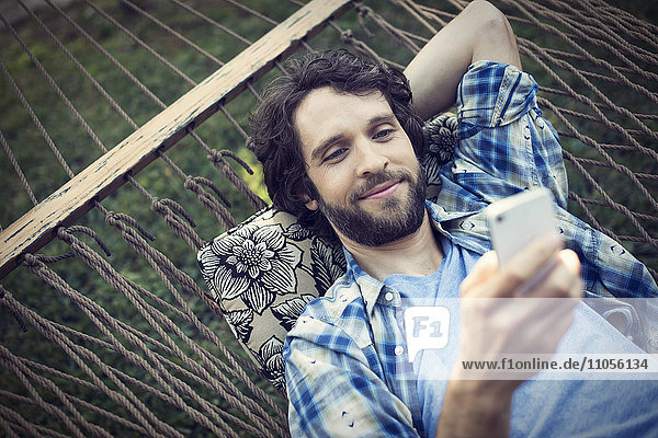 A man lying in a garden hammock taking selfies with his phone.