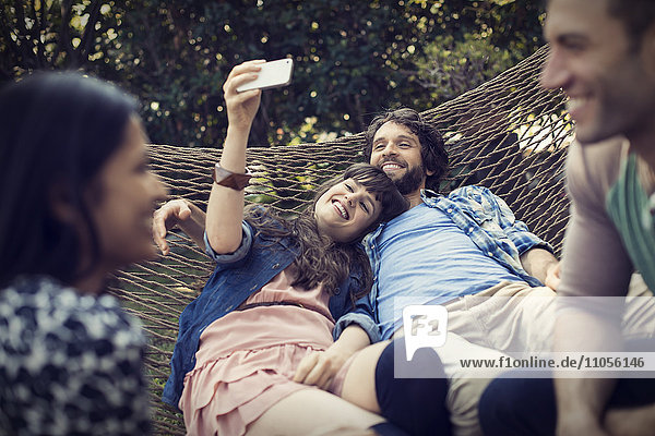 A group of friends lounging in a large hammock in the garden having a beer  and taking a selfie.