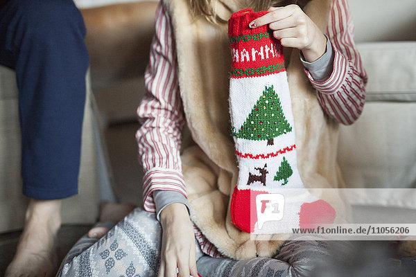 Zwei Personen packen am Weihnachtsmorgen Geschenke mit Weihnachtsstrümpfen aus.