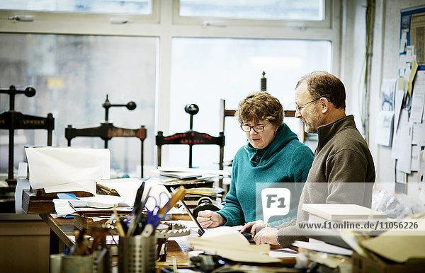 Zwei Personen arbeiten in einer Buchbinderei. Umgeben von Werkzeugen und Buchpressen.