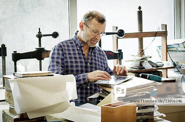 Ein Mann benutzt ein digitales Tablett in einer Buchbinderei.