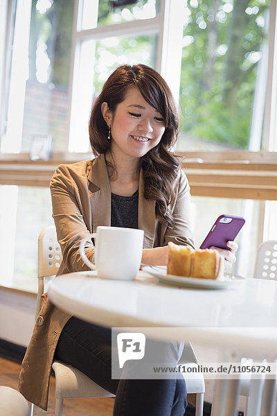 Smiling young woman sitting at a table with a mug and slice of cake  looking at her smart phone.