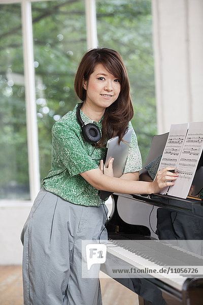 Young woman standing next to a grand piano in a rehearsal studio  holding sheet music.