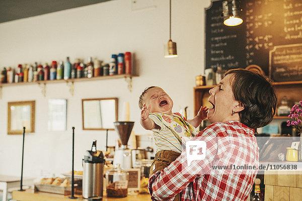 Eine Frau  die in einem Café ein weinendes Baby hält.