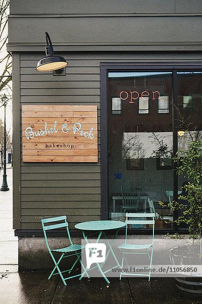 Das Äußere eines kleinen Geschäfts  Straßenansicht  eines Cafés mit Tisch und Stühlen im Freien.